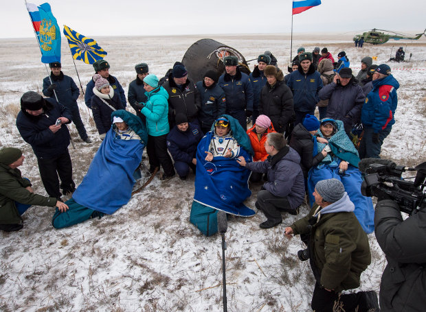 Alexander Gerst, Maksim Surayev and Gregory Reid Wiseman assisted after landing in the Soyuz TMA-13M spacecraft (Photo NASA/Bill Ingalls)