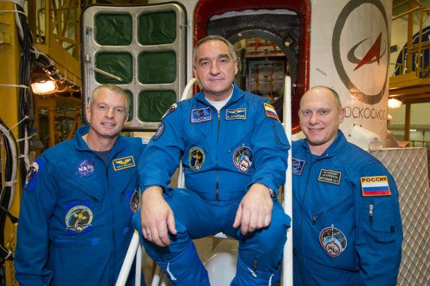 Steve Swanson, Alexander Skvortsov and Oleg Artemyev in front of their Soyuz TMA-12M spacecraft on March 21 (Photo NASA/Victor Zelentsov)
